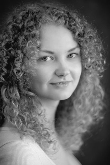 Smiling fairy woman with curly hair, big breast on dark grey background black&white vertical portrait