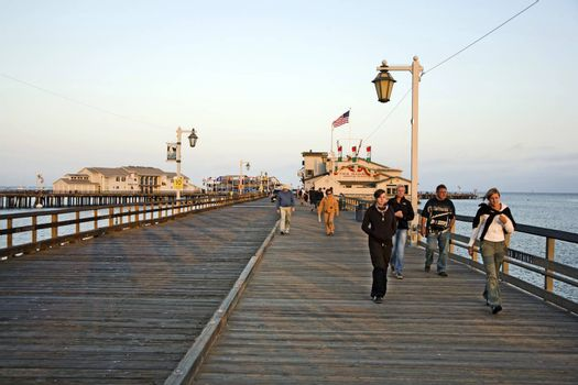 SANTA BARBARA, USA - JULY 28, 2008: people visiting scenic pier in Santa barbara in sunset   in Santa Barbara, USA. First built in 1872, the wharf ranked as the longest deep-water pier.