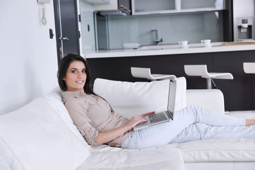 relaxed young woman working on laptop computer in bright  home indoor