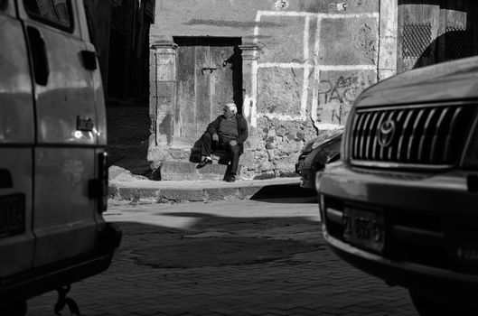 LEONFORTE, ITALY - JANUARY, 08: Old man sitting on the step of old door on January 08, 2014