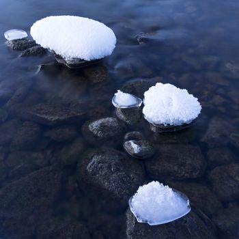 Snow-covered stones in the water. Lake Teletskoye, Altai Republic, Russia