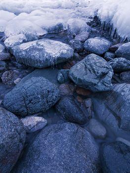 Ice-covered stones in the water. Lake Teletskoye, Altai Republic, Russia