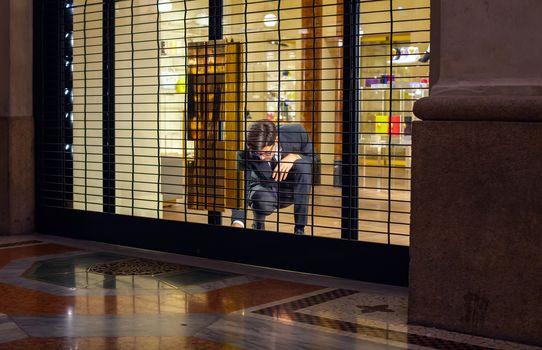 MILAN, ITALY - NOVEMBER, 24: Salesman close shop shutter on November 24, 2014