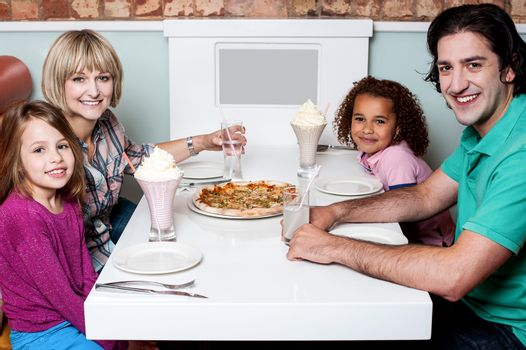 Happy couple and their children sitting in restaurant