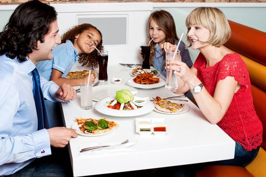 Happy family of four together in a restaurant