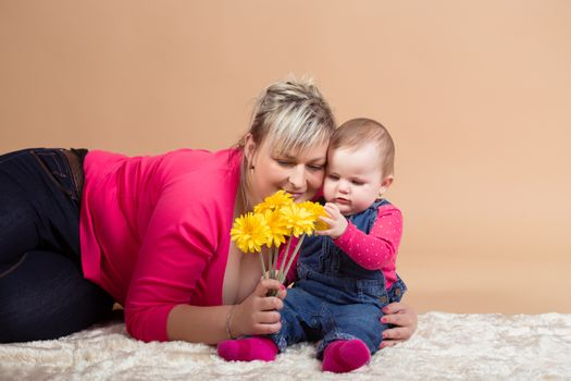 infant baby with his mom and yellow flowers- the first year of the new life