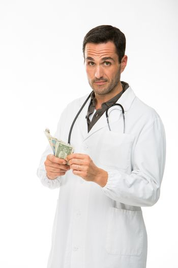 Half length portrait of a male doctor with stethoscope while counting money