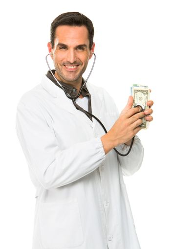 Half length portrait of a male doctor, smiling at camera and using stethoscope on money