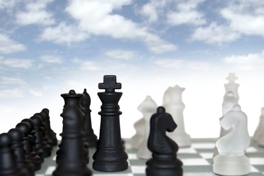 chess pieces isolated against a cloudy blue sky background