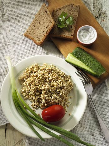 Tasty and healthy buckwheat dish with bread, onion, cucumber