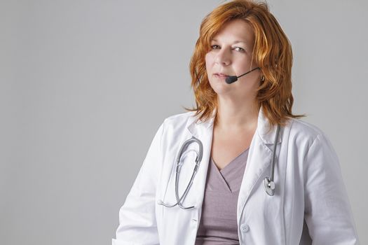 forty something woman doctor with red hair with a stethoscope and a headset
