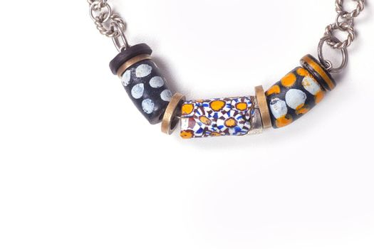 Close up of silver and painted stone necklace isolated on white background, manufactured by Ornella Salamone