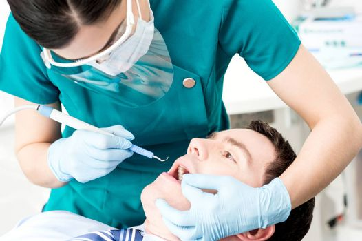 Female dental assistant treat male patient in clinic