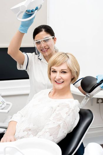 Dentist assistant and female patient looking at camera