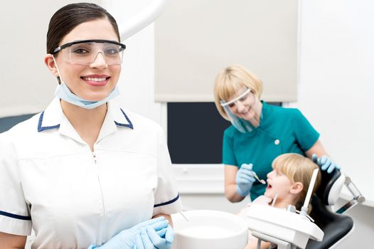 Smiling dentist, assistant examining a patient behind