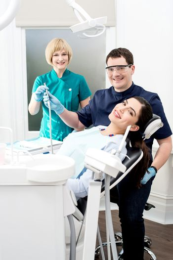 Woman at dental clinic with doctor and his assistant