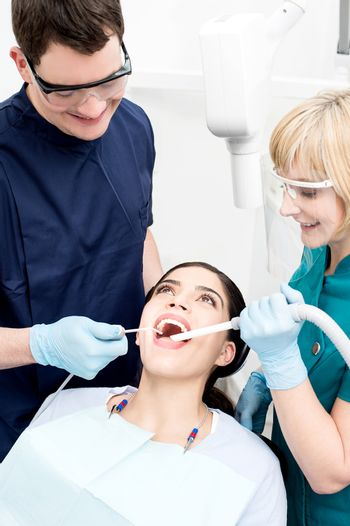 Female patient receiving dental care from doctor