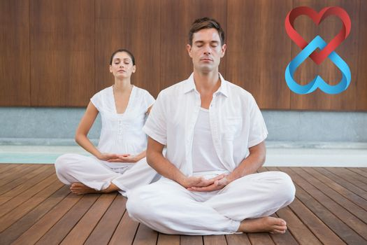 Peaceful couple in white sitting in lotus pose together against linking hearts