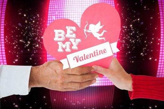 Couple holding heart against glittering screen on black background