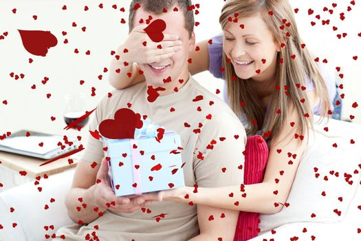 Smiling woman giving a present to her boyfriend against love heart pattern