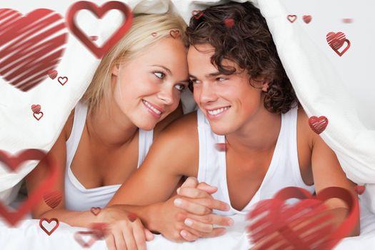 Portrait of an in love couple under a duvet against love heart pattern