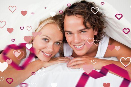 Couple under a duvet against love heart pattern