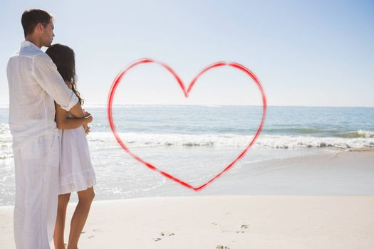 Attractive couple looking out at sea against heart
