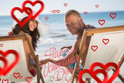 Cute couple looking while lying on their deck chairs against happy valentines day