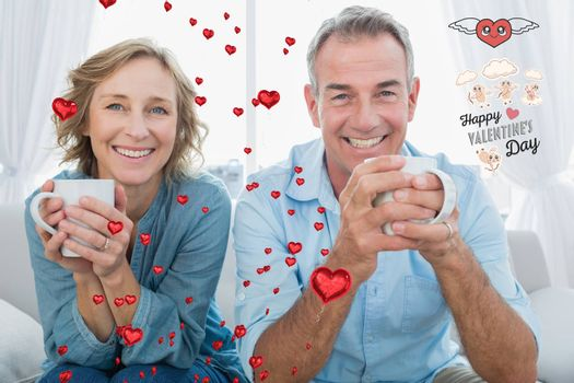 Smiling middle aged couple sitting on the couch having coffee against cute valentines message