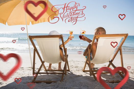 Happy couple drinking cocktails while relaxing on their deck chairs against happy valentines day