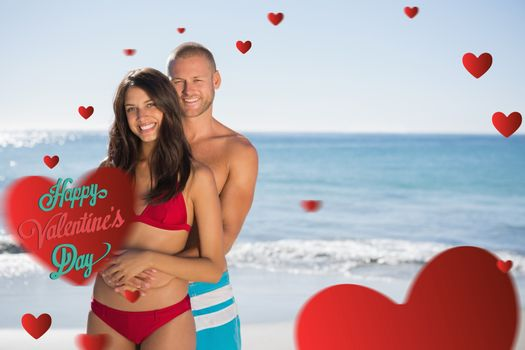 Loving couple embracing one another  against happy valentines day