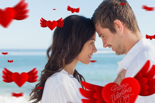 Attractive couple embracing on the beach  against cute valentines message