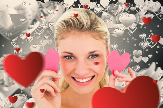 Attractive young blonde holding little hearts  against grey valentines heart pattern