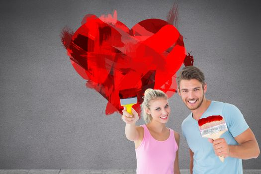 Young couple smiling and holding paintbrushes  against grey room