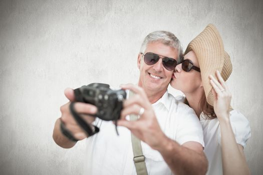 Vacationing couple taking photo against white background