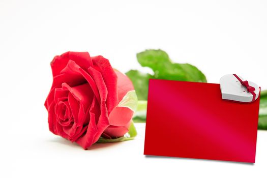 Composite image of red rose with stalk and leaves lying on surface