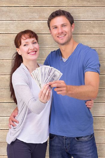 Couple holding fan of cash against wooden planks