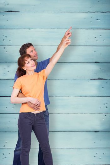 Happy couple pointing upwards together against wooden planks