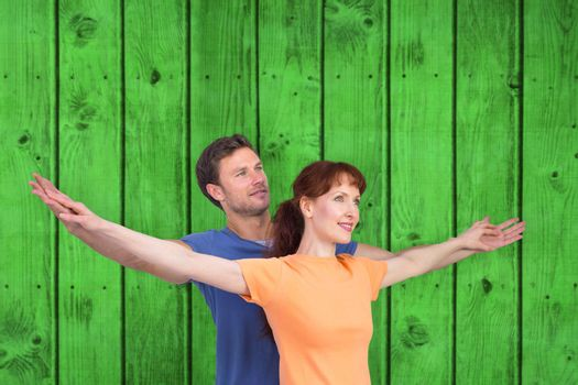Happy couple looking upwards against bright green wooden planks