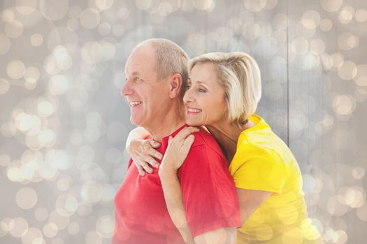 Happy mature couple hugging and smiling against light glowing dots design pattern