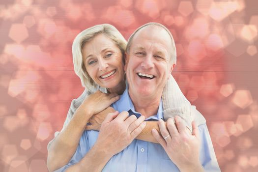 Happy mature couple embracing smiling at camera against light glowing dots design pattern