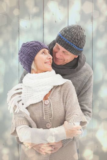 Happy mature couple in winter clothes embracing against light glowing dots design pattern