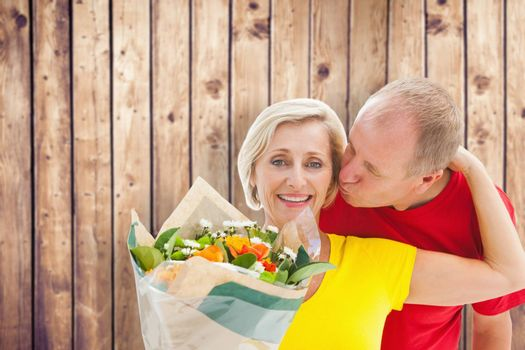 Mature man kissing his partner holding flowers against wooden planks