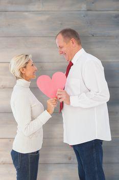 Older affectionate couple holding pink heart shape against pale grey wooden planks