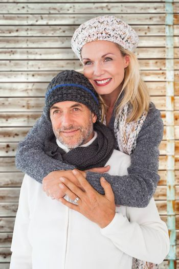 Happy couple in winter fashion embracing against faded pine wooden planks