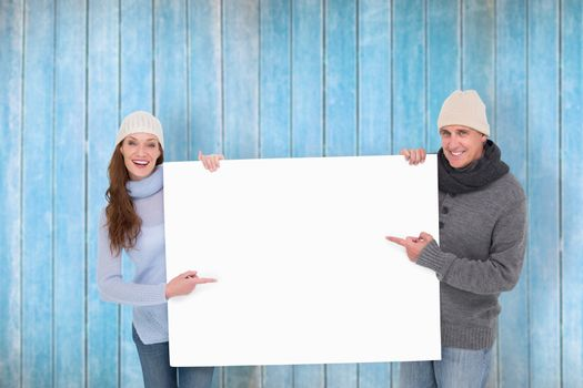 Composite image of casual couple in warm clothing holding poster