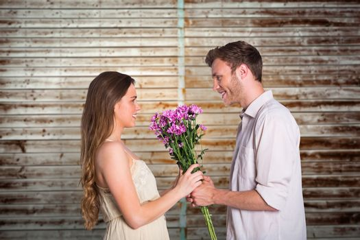 Side view of couple holding flowers against wooden planks