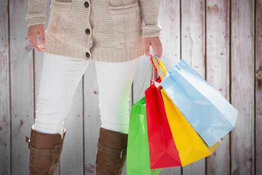 Woman with shopping bags against wooden planks