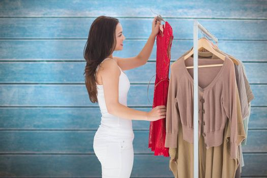 Woman choosing clothes against wooden planks