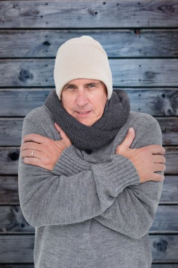 Composite image of casual man shivering in warm clothing